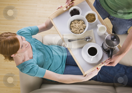 Attractive woman being served breakfast on the couch. stock photo, Attractive woman being served on couch. Top view, horizontally framed shot. by Jonathan Ross