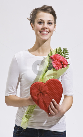 Attractive woman and valentines day gifts stock photo, Attractive woman with flowers and heart-shaped candy box. Vertically framed shot. by Jonathan Ross