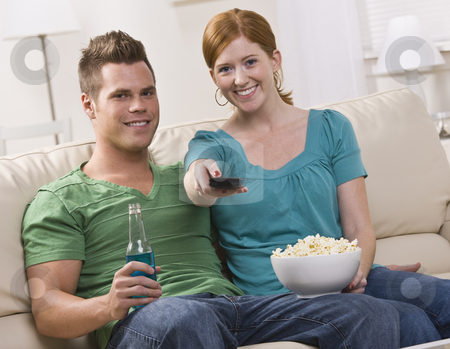 Attractive couple watching TV stock photo, Attractive couple watching TV eating popcorn. horizontal by Jonathan Ross