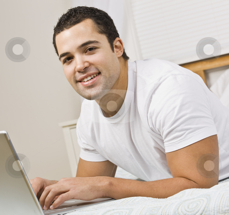 Man Using Laptop stock photo, A man relaxing on a bed and using a laptop computer.  He has his fingers on the keyboard and is smiling at the camera. Square framed shot. by Jonathan Ross
