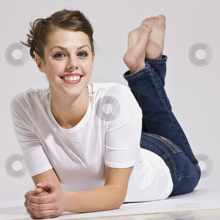 Attractive Woman Lying Down and Smiling stock photo, An attractive young female posing for a picture.  She is resting on her stomach and is smiling. Square. by Jonathan Ross