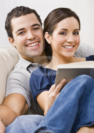 Couple Relaxing stock photo, An attractive young couple relaxing together.  The female is holding a book and they are smiling directly at the camera. Vertically framed photo. by Jonathan Ross