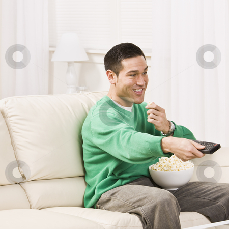 Man Watching Television stock photo, A man seated on a couch and using a remote control for T.V. He is eating popcorn and smiling. Square framed photo. by Jonathan Ross