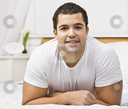 Attractive man on bed stock photo, Brunette male on bed laying on stomach.square by Jonathan Ross