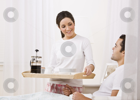 Woman Serving Breakfast Tray to Man stock photo, A beautiful young woman serving a breakfast tray to a man lying in bed.  They are smiling happily at one another. Horizontally framed shot. by Jonathan Ross