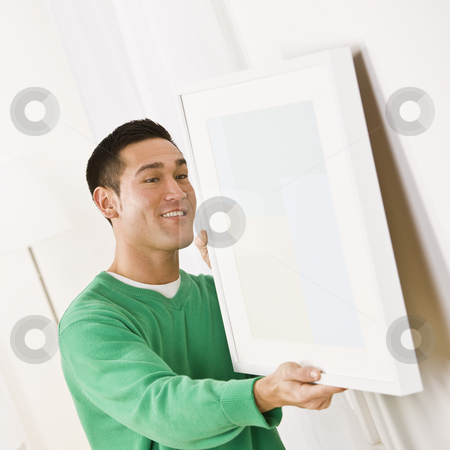 Asian male hanging art stock photo, Asian male wearing a green sweater hanging art on wall. Square composition by Jonathan Ross