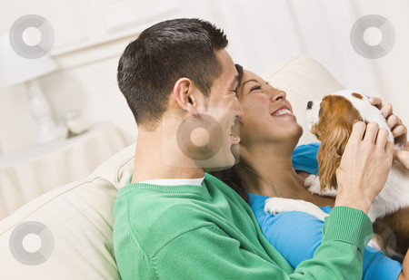 Laughing Couple Holding Dog stock photo, An attractive young couple sitting on a couch together and holding a dog.  They are laughing.  Horizontally framed shot. by Jonathan Ross