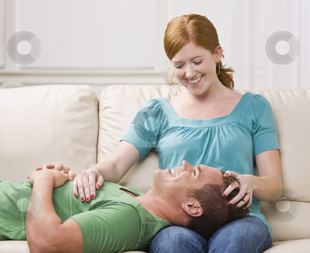 Cute Couple Lounging stock photo, A cute young couple lounging on a couch together. The female is holding the male's head on her lap.  They are laughing and looking at one another. Square framed shot. by Jonathan Ross