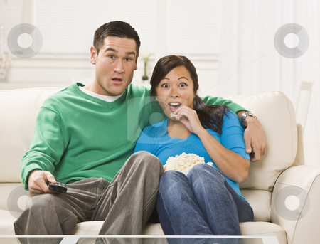 Surprised Couple Watching TV stock photo, A shocked or surprised looking young couple watching television together.  They are seated on a couch and have a bowl of popcorn. The man is holding a remote control and they are looking directly at the camera. Horizontally framed shot. by Jonathan Ross