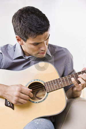 Man Playing an Acoustic Guitar stock photo, An attractive young man playing the acoustic guitar.  He is looking down at the guitar.  Vertically framed shot. by Jonathan Ross