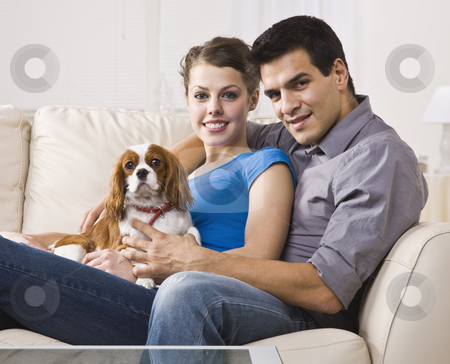Couple with Dog stock photo, An attractive young couple sitting on a couch together and holding a dog. They are smiling and looking directly at the camera. Horizontally framed photo. by Jonathan Ross