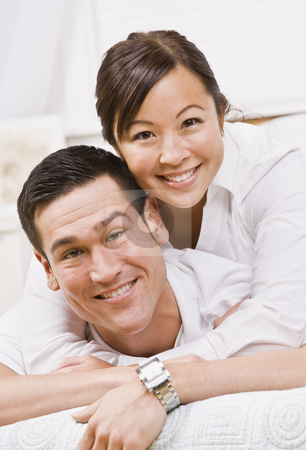 Attractive Couple Hugging and Smiling at the Camera stock photo, An attractive young couple posing.  They are wearing white and are looking directly at the camera. Vertically framed photo. by Jonathan Ross