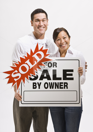 Attractive couple with sold sign stock photo, Attractive couple holding sold sign for home. Vertically framed by Jonathan Ross
