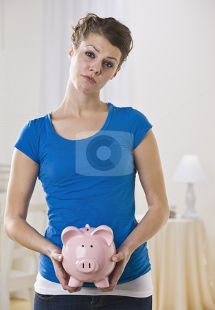 Female Holding Piggy Bank stock photo, A young female holding a piggy bank.  She is facing the camera and has a worried look on her face. Vertically framed photo. by Jonathan Ross