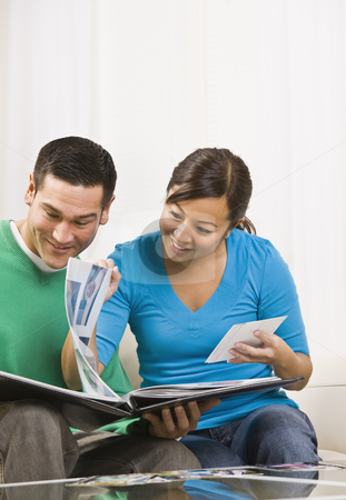 Happy Couple Viewing Photos stock photo, An attractive young couple sitting on a couch and viewing a photo album together.  They are smiling. Vertically framed shot. by Jonathan Ross