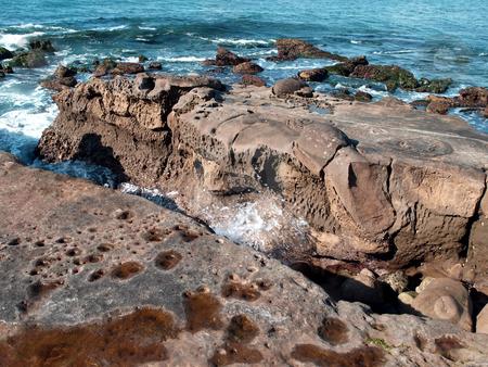 Waves splash between large coastal rocks stock photo, Waves and surf splash through large costal coral formations by Jill Reid