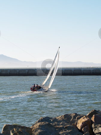 Sailboat close hauled heading out under sail from marina stock photo, Sailboat leaving marina with breakwater under sail by Jeff Cleveland