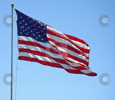 American Flag Flying Against Blue Sky stock photo, This American flag is flying it's red, white and blue symbol against a bright blue sky. by Valerie Garner
