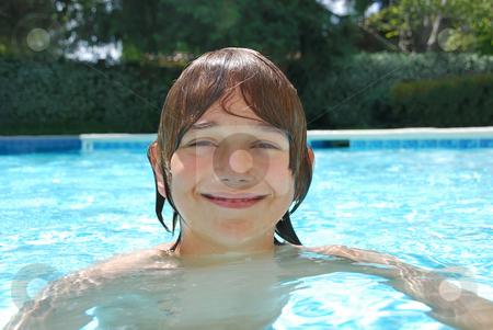 Smiling Teenage Boy Swimming in Pool stock photo, Smiling teenage boy swimming in the pool surrounded with white flower bushes in the background. by Denis Radovanovic