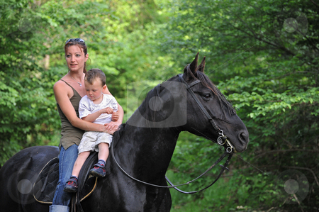 Mother, son and black horse stock photo, Young woman, little boy and their black stallion in a forest by Bonzami Emmanuelle