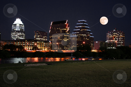 Downtown Austin, Texas at Night with Moon stock photo, A very pretty night in Austin, Texas.  This shot was taken from across Town Lake downtown.  A very useful image for Austin related content.  The moon was adding in for effect. by Brandon Seidel