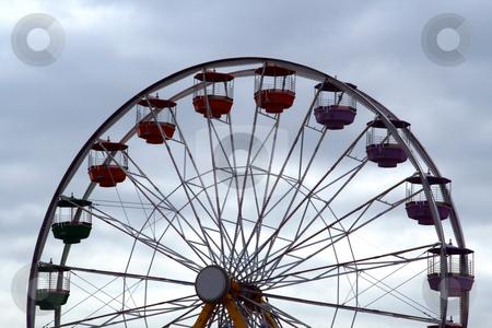 Ferris Wheel against a cloudy sky stock photo, A ferris wheel against a cloudy sky by Brandon Seidel