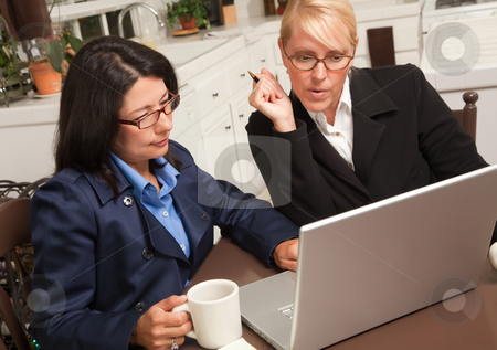 Businesswomen Working on the Laptop stock photo, Businesswomen Working on the Laptop Together in the Kitchen. by Andy Dean