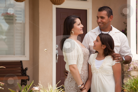 Small Hispanic Family in Front of Their Home stock photo, Small Hispanic Mother, Father and Daughter in Front of Their Home. by Andy Dean