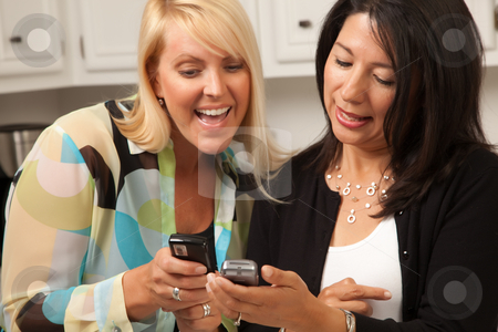 Two Girlfriends Sharing with Their Cell Phones stock photo, Two Girlfriends Sharing with Their Cell Phones in the Kitchen. by Andy Dean