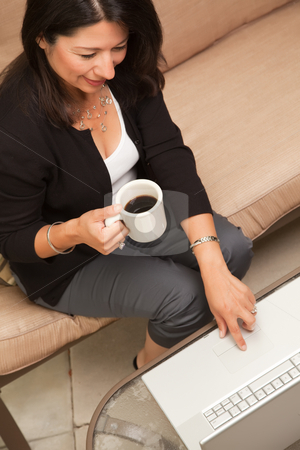 Hispanic Woman with Coffee and Laptop stock photo, Hispanic Woman with Coffee and Laptop On Her Patio. by Andy Dean