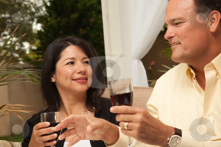 Hispanic Woman and Caucasian Man Enjoying Wine stock photo, Hispanic Woman and Caucasian Man Enjoying Wine on the Patio. by Andy Dean