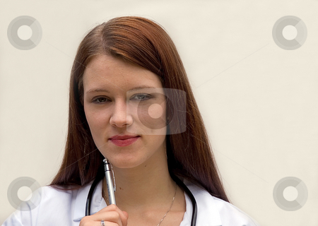 Young Woman Medical Doctor stock photo, This young brunette Caucasian medical doctor is holding a pen and wearing a stethoscope against a light background. by Valerie Garner