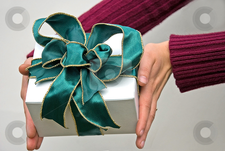 Hands Holding Gift with Green Bow stock photo, Hands are holding a gift of a white box and deep green wire edged ribbon bow with metallic gold edges. by Valerie Garner