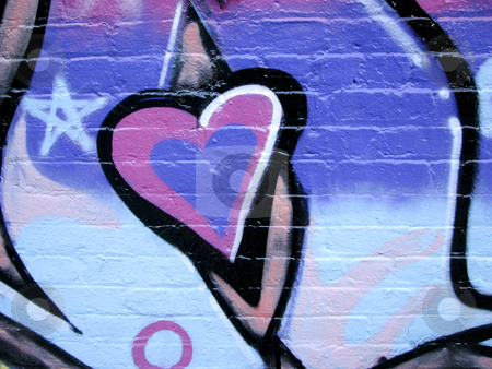 Painted heart on brick wall stock photo, Graffiti purple and pink painted heart on brick wall by Annette Davis