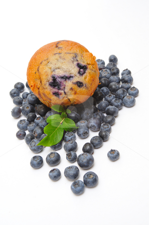Blueberry Muffin stock photo, Fresh blueberries surround a single blueberry muffin on a light background by Lynn Bendickson