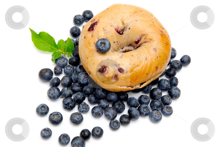 Blueberry Bagel stock photo, Fresh blueberries surround a single blueberry bagel on a light background by Lynn Bendickson