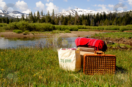 Meadow Picnic stock photo, Ingredients for a picnic at a mountain meadow, picnic basket, ice chest, red blanket and ecoligically freindly re-usable shopping bag to carry other items by Lynn Bendickson