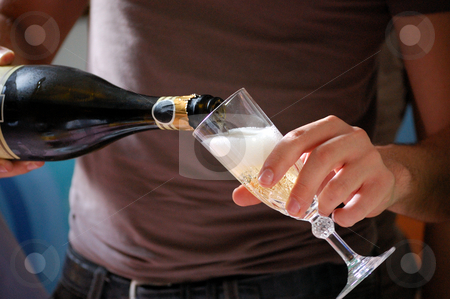 Serving champagne stock photo, A man is serving champagne in a crystal glass by ALESSANDRO TERMIGNONE