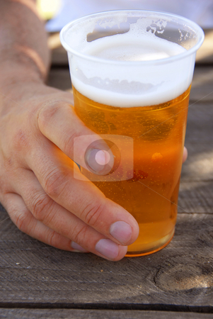 Beer in plastic glass stock photo, Orange beer in transparent plastic glass in man hand closeup outdoor by Julija Sapic