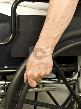 Older hand on wheel chair pushing stock photo, Older hand on wheel chair pushing by John Teeter