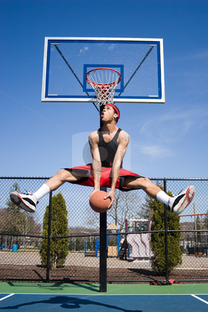 Man Playing Basketball stock photo, A young basketball player driving to the hoop with some fancy moves. by Todd Arena