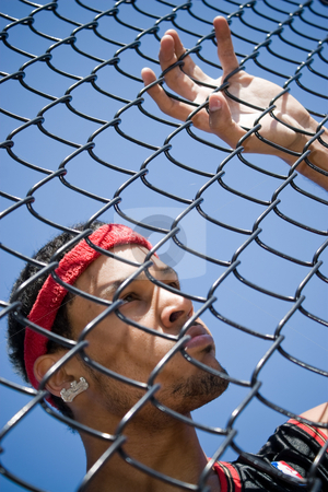 Basketball Player stock photo, This young basketball player leans up against a chain linked fence at the basketball court. by Todd Arena