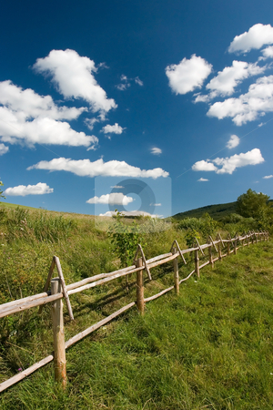East European summer landscape stock photo, East European summer landcape with wooden fence and beautiful clouds by Wiktor Bubniak