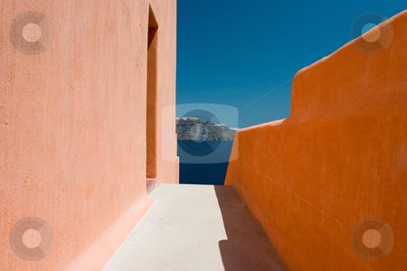 Narrow sidewalk  stock photo, Narrow sidewalk between orange walls and island city afar off by Wiktor Bubniak