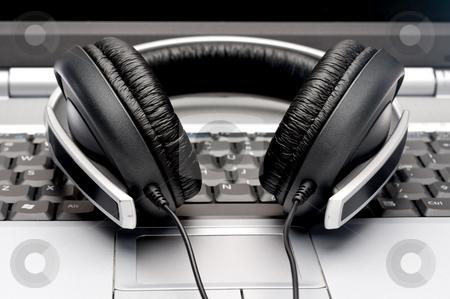 Horizontal image of silver colored headphones on a notebook comp stock photo, Horizontal image of silver colored headphones on a notebook computer by Vince Clements