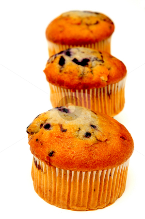 Three Muffins stock photo, Blueberry muffins lined up in a row on a light colored background by Lynn Bendickson