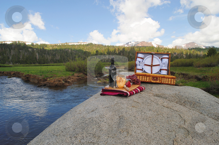 Picnic On The River stock photo, Fruit and Wine picnic in a scenic mountain setting with a meadow and river in the background by Lynn Bendickson