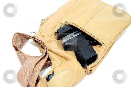 Purse And Handgun stock photo, A light brown womens purse with a .45 caliber pistol, the magazine removed showing the hollow point cartridge in detail with a cell phone in the shoulder strap pouch on a light colored background by Lynn Bendickson