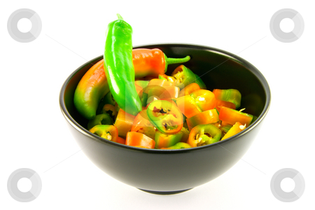 Chillis stock photo, Two chillis and chopped chillis in a black bowl with clipping path on a white background by Keith Wilson