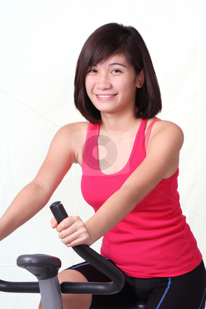 Spin bike lady stock photo, Young asian lady exercising on a stationary bike by Claro Alindogan